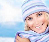 Photo of cute blond girl wearing blue warm beanie and scarf, closeup portrait of nice woman dressed
