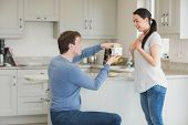 Woman getting a present from husband on one knee in kitchen