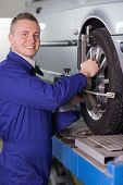 Smiling mechanic changing a car wheel in a garage