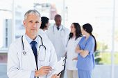 picture of mature adult  - Mature doctor pointing seriously at something on his clipboard - JPG