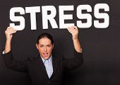 Stressed angry attractive businesswoman holding up the word STRESS in white lettering high above her head on a black studio background