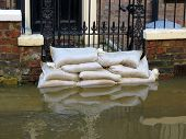 Sandbags stacked in front of house in York flooded street.