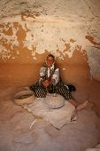foto of cave-dweller  - A Happy native woman grinds corn in her house - JPG