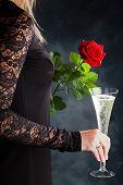 eine Frau im Abendkleid mit einer roten Rose und einem Glas Sekt oder Champagner