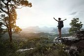 Young hiker with backpack standing with raised hands on a cliff's edge and looking over wild tropica