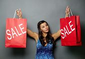 Portrait of pretty brunette holding sale paperbags