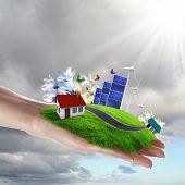 Hände halten eine grüne Erde mit solar batareis