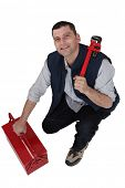 Tradesman with a pipe wrench and toolbox