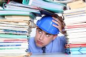 Architect surrounded by piles of paperwork