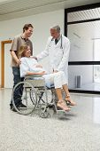 Doctor is talking to a pregnant patient in a wheelchair in the corridor of the hospital