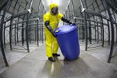 Worker in protective uniform,mask,gloves and boots rolling barrel of chemicals in empty storehouse -
