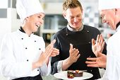 Chef team in restaurant kitchen with dessert, the colleagues applauding because the dish works great