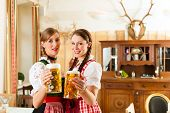 picture of stein  - Two young women in traditional Bavarian Tracht in restaurant or pub with beer and beer stein - JPG