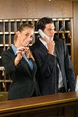 Reception in hotel - Man and woman standing at the front desk, man taking a call, woman holding a key in the hand and smiling