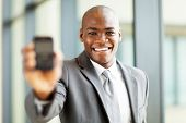 african american businessman holding a smart phone towards the camera