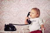 little baby with old vintage phone before retro background