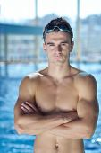 Happy muscular swimmer wearing glasses and cap at swimming pool and represent health and fit concept