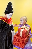 Happy little clown with big presents and sad pierrot with a small gift