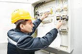 One electrician builder at work with assembly drawing inspecting high voltage power electric line distribution fuseboard