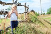 Embarrassed Small Girl Standing In Front Of Rural Fence. Copyspace