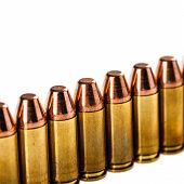 picture of 9mm  - a lot of 9mm bullets arranged in a row and isolated over a white background - JPG