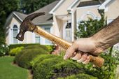Man's hand holding hammer in front of a house indicating home improvement and maintenance.