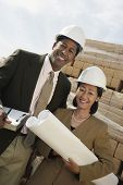 Portrait of two multiethnic surveyors with blueprint on construction site