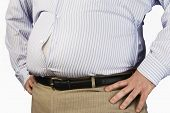 stock photo of bulging belly  - Closeup midsection of an overweight man standing with unbuttoned shirt and hands on hip - JPG
