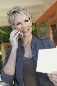 Elegant middle aged woman using mobile phone with brochure in hand