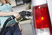 Closeup midsection of a woman refueling her car at the gas station