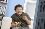 Smiling overweight boy eating bowl of fruit in front of television