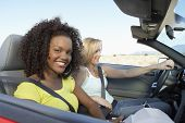 stock photo of seatbelt  - Two happy multiethnic women sitting in convertible on desert road - JPG