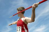 Male athlete about to throw javelin against the sky