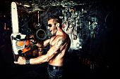 stock photo of chainsaw  - Expressive handsome muscular man with a chainsaw in the old garage - JPG