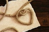 'Tying the knot' wedding invitation or save the date card.  Rope knotted into a heart shape with han