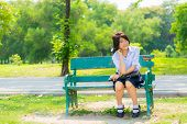 Shy Thai Schoolgirl Sitting On A Bench