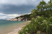 Storms Gather Over A Tropical Paradise Beach.