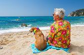 Senior man sitting with dog on tropical beach