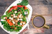 picture of leafy  - Bowl of fresh leafy green baby spinach and tomato salad with a freshly brewed mug of hot tea on a rustic wooden table overhead view - JPG
