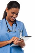 foto of prescription pad  - Female physician in uniform operating tablet pc device - JPG