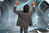 Businessman standing with arms pressing up against blue abstract design in structure