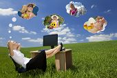 Business concept shot of a beautiful young woman relaxing at a desk in a green field day dreaming, o