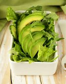 green salad with avocado and arugula in a white bowl