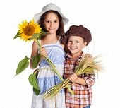 Two kids with sunflower and stalks of wheat