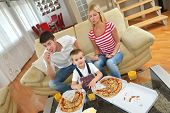 happy young family eating tasty pizza with cheesa and dring healthy and fresh orange juice