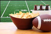 Chips, football and Six Pack of Beer on a table in front of a big screen TV with a Football field. G