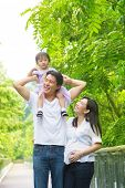 Happy Asian family outdoor. Father piggybacking his daughter walking in garden park with pregnant wife. Healthy lifestyle.