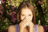 stock photo of allergy  - Young woman with allergy during sunny day is wiping her nose - JPG