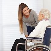 Young woman talking to smiling senior citizen in a wheelchair
