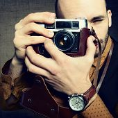 Photographer. Portrait of handsome stylish man in trendy clothes taking photo with retro camera, vintage toned